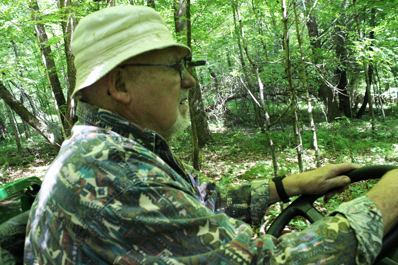 John Rylander driving a 4-wheel ATV through trails in the 40-acre woods. Photo: Jamie L. Manser